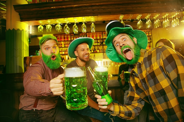 Festa do dia de são patrício. amigos felizes estão comemorando e bebendo cerveja verde.