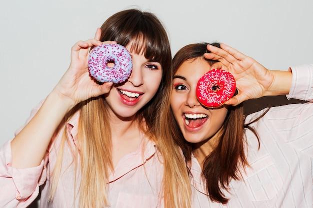 Festa do pijama em casa. feche o retrato em flash de duas mulheres brancas engraçadas posando com donuts. rosto de surpresa.