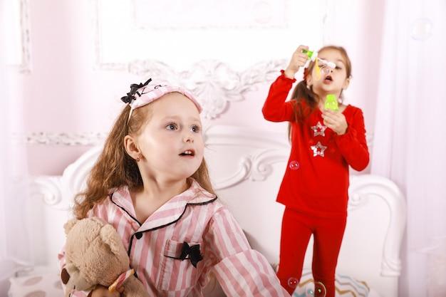 Festa do pijama para crianças, meninas-crianças vestidas de pijama brilhante, jogo de bolhas