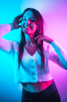 Festa em uma boate com luzes de néon rosa azul, uma jovem morena caucasiana se divertindo em um suéter de lã branca