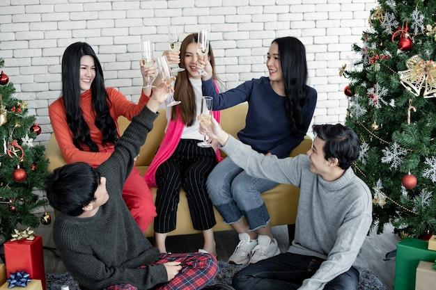 Festa engraçada de jovens asiáticos com copos de clink e bebeu vinho em casa para comemorar o festival de natal. celebração de ano novo em casa. feliz natal e boas festas de gangue teen thai.