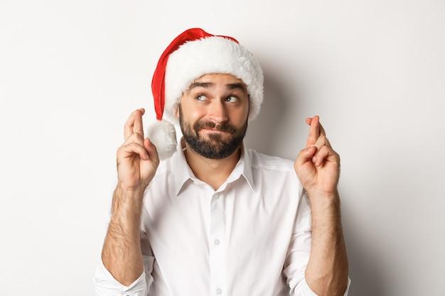 Festa, férias de inverno e conceito de celebração. homem feliz com chapéu de papai noel fazendo desejo de natal, dedos cruzados para boa sorte e parecendo esperançoso no canto superior esquerdo.