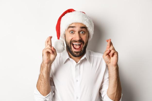 Festa, férias de inverno e conceito de celebração. homem feliz com chapéu de papai noel fazendo um desejo de natal, cruze os dedos para dar sorte e parece animado