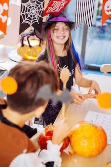 Festa incrível. irmão e irmã vestindo fantasias de halloween, participando de uma festa incrível com muitas decorações brilhantes