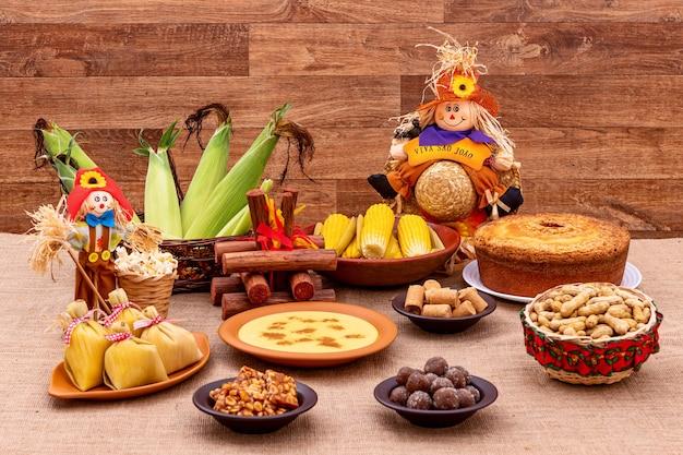 Festa junina brasileira. comidas típicas da festa junina. canjica, milho cozido, bolo de milho, pipoca, brócolis, paçoca, jenipapo e amendoim. está escrito: viva são joão em português.