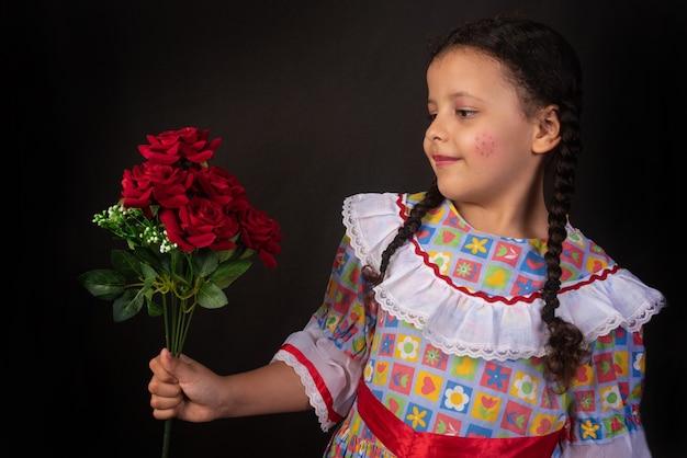 Festa junina no brasil, menina brasileira com tranças e vestida para festa junina com buquê de flores na mão.