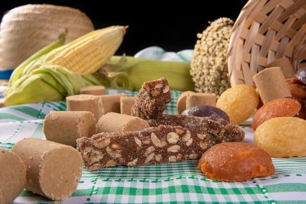 Festa junina no brasil, mesa com vários doces em toalha xadrez verde e branca.