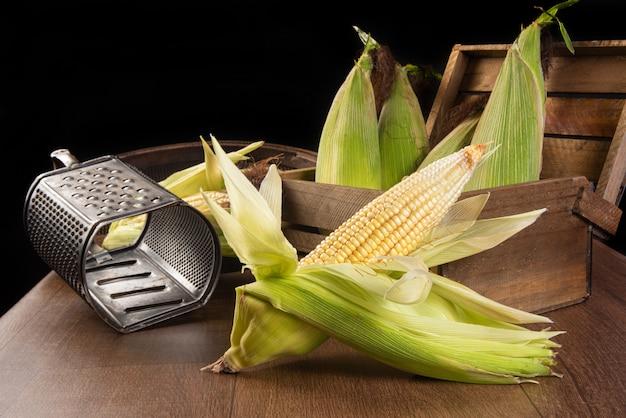 Festa junina no brasil, milho verde, ralador e peneira na mesa.