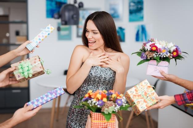 Festa surpresa. menina cercada por flores dos presentes.