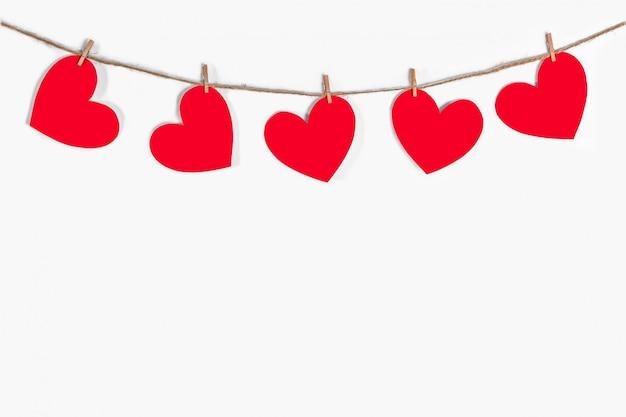 Festão de corações vermelhos em um fundo branco e isolado. corda natural e prendedores de roupa. o conceito de reconhecimento no amor, relacionamentos românticos, dia dos namorados. copie o espaço