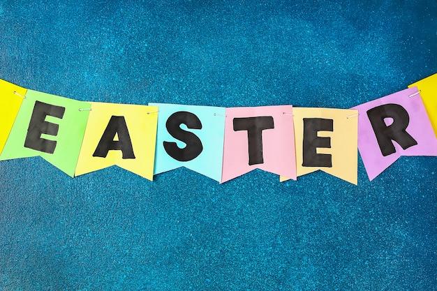 Festão de diy easter, bandeiras easter fez o papel o fundo azul.