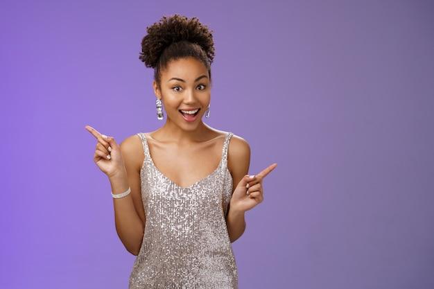 Festeira afro-americana encantadora de saída divirta-se dançando apontando diferentes lados direita esquerda mostrar opções variantes sorrindo amplamente pedindo conselhos para que lado ir, em pé de fundo azul.