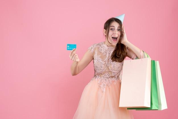 Festeira com chapéu de festa segurando um cartão e sacolas de compras colocando a mão perto de sua bochecha no rosa
