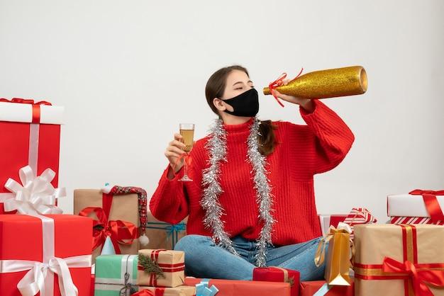 Festeira com máscara preta segurando champanhe sentada em volta de presentes em branco