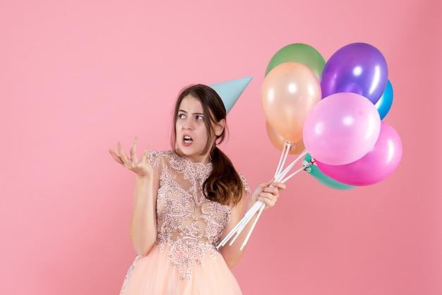 Festeira de vista frontal com boné segurando balões algo