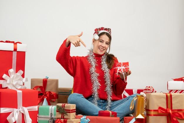 Festeira de vista frontal com chapéu de papai noel apontando para o presente dela sentada em volta de presentes