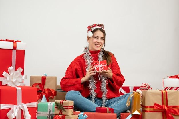 Festeira de vista frontal com chapéu de papai noel segurando um presente com as duas mãos sentadas em volta dos presentes
