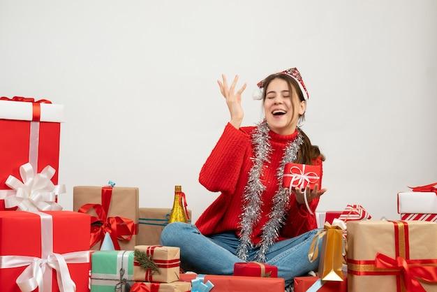Festeira de vista frontal com chapéu de papai noel segurando um presente e rindo sentado em volta dos presentes