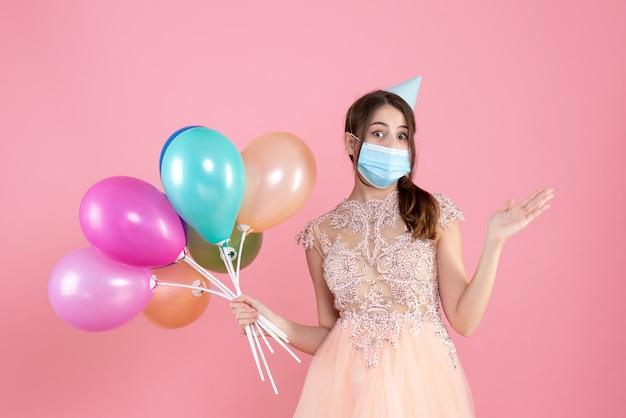Festeira de vista frontal com tampa de festa segurando balões coloridos apontando para algo