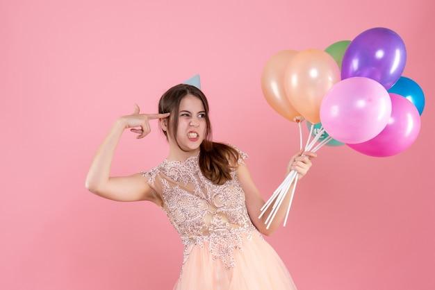 Festeira de vista frontal confusa com boné de festa segurando balões e segurando uma arma de dedo perto de sua têmpora