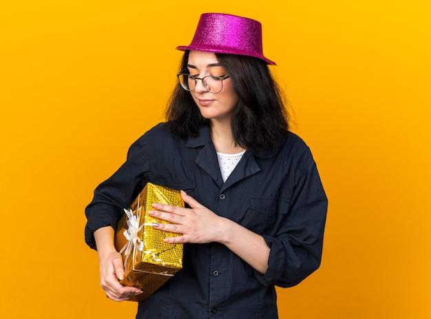 Festeira jovem caucasiana com chapéu de festa e óculos, segurando e olhando para um pacote de presente isolado na parede laranja