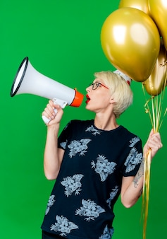 Festeira jovem de óculos e boné de aniversário segurando balões, virando-se de frente para os lados, falando por alto-falante isolado sobre fundo verde
