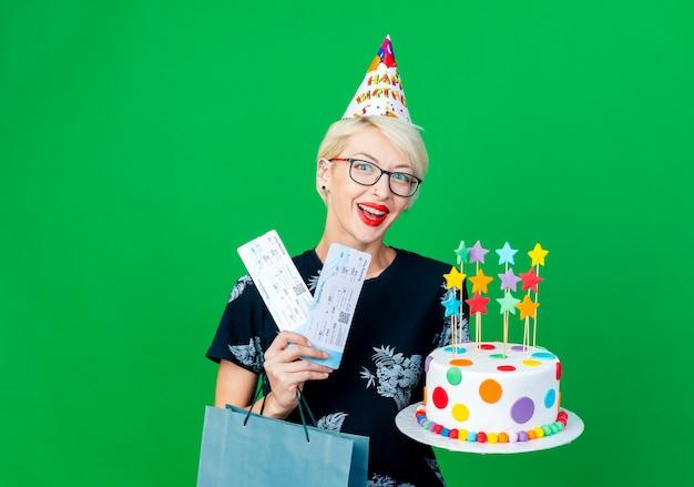Festeira jovem loira impressionada de óculos e boné de aniversário segurando um bolo de aniversário com passagens de avião de estrelas e um saco de papel olhando para a câmera isolada em um fundo verde com espaço de cópia