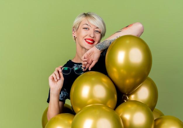 Festeira jovem loira sorridente em pé atrás de balões segurando óculos, colocando o braço em um balão, olhando para a câmera isolada em fundo verde oliva com espaço de cópia