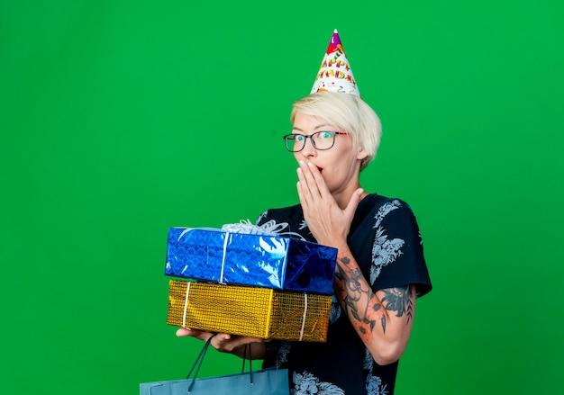 Festeira jovem loira surpresa de óculos e boné de aniversário, segurando um saco de papel e caixas de presente, olhando para a câmera, mantendo as mãos na boca isolada no fundo verde com espaço de cópia