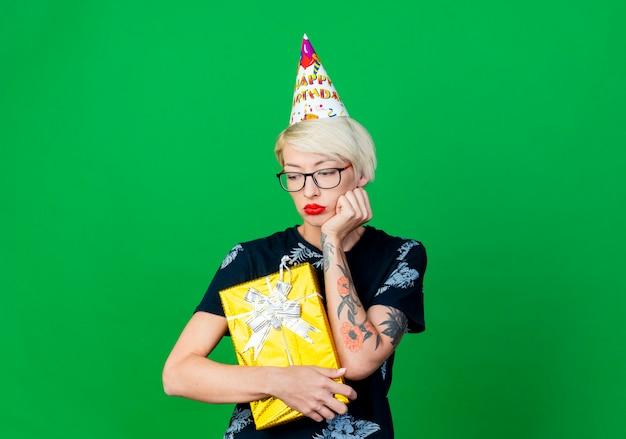 Festeira jovem loira triste usando óculos e boné de aniversário segurando uma caixa de presente, olhando para baixo, isolada em um fundo verde com espaço de cópia