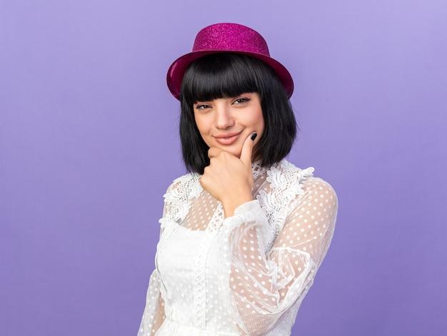 Festeira jovem pensativa com chapéu de festa em pé em vista de perfil, olhando para frente, mantendo a mão no queixo isolada na parede roxa com espaço de cópia