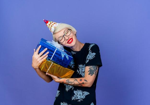Festeira jovem sorridente de óculos e boné de aniversário segurando caixas de presente e colocando a cabeça nelas com os olhos fechados, isolado no fundo roxo com espaço de cópia