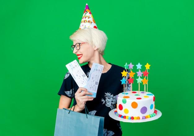 Festeira jovem sorridente de óculos e boné de aniversário segurando um bolo de aniversário com bilhetes de avião de estrelas e um saco de papel com os olhos fechados, isolado em um fundo verde com espaço de cópia