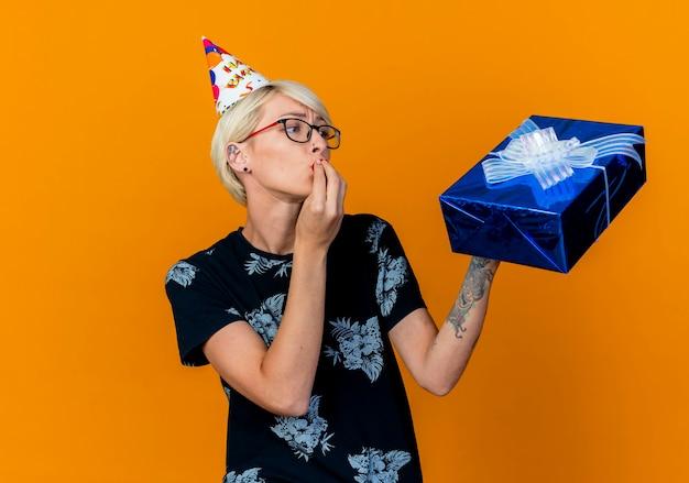Festeira jovem usando óculos e boné de aniversário segurando e olhando para uma caixa de presente, fazendo um gesto de beijo isolado em um fundo laranja com espaço de cópia