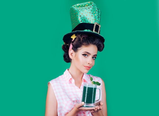 Festeira na mulher pin-up de patricks day em estilo verde com cerveja.