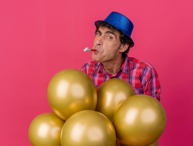Festeiro duvidoso de meia-idade usando chapéu de festa em pé atrás de balões olhando para frente com um soprador de festa na boca isolado na parede carmesim