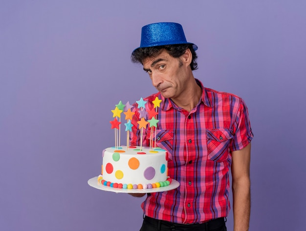 Festeiro duvidoso de meia-idade usando um chapéu de festa segurando um bolo de aniversário, olhando para a frente, isolado na parede roxa