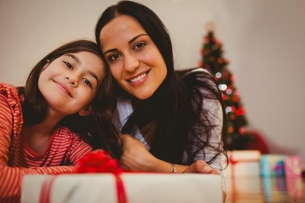 Festiva mãe e filha sorrindo na câmera