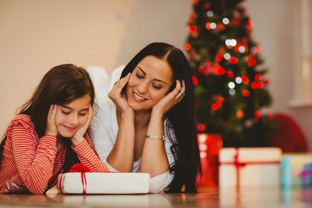 Festiva mãe e filha sorrindo no presente