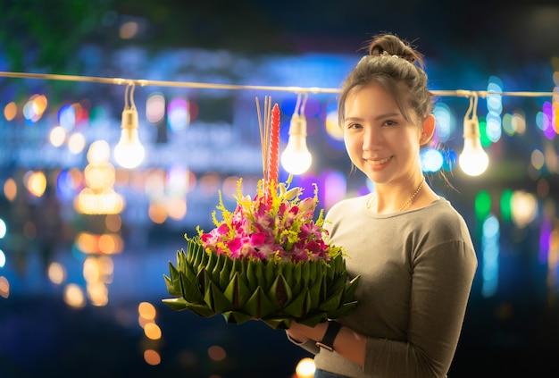 Festivais de loy krathong na tailândia mulher bonita segura krathong com folha de bananeira para acreditar que boa sorte e obrigado rio de água
