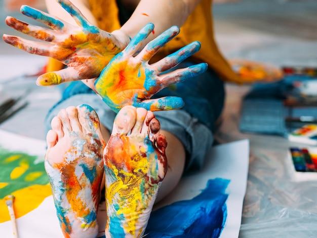 Festival de arte moderna. foto recortada do artista sentado no chão, mostrando os pés e as mãos sujas com tinta multicolor. desfocar o fundo.