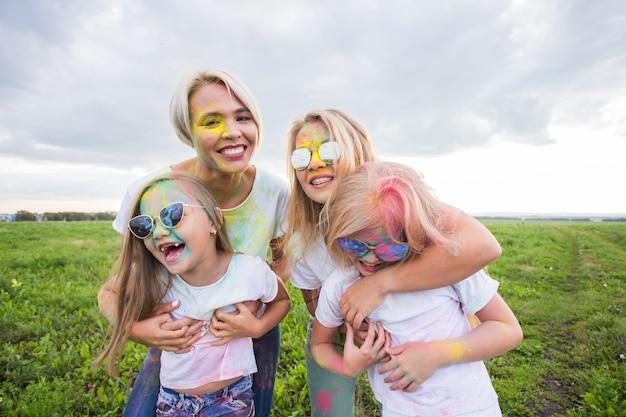 Festival de holi, conceito de amizade e férias - jovens do sexo feminino na cor, dançando e se divertindo.