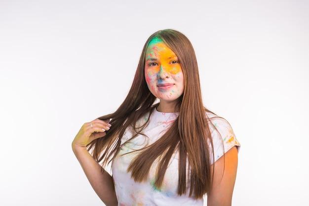 Festival de holi, conceito de pessoas - jovem suja em cores sorrindo e se divertindo em branco