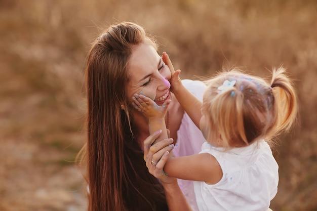 Festival de holi, divertido e conceito de pessoas - mãe e filha pequena brincando com pó colorido juntos