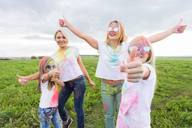 Festival de holi, feriados e conceito de felicidade - adolescentes e mulheres coloridas se divertem ao ar livre
