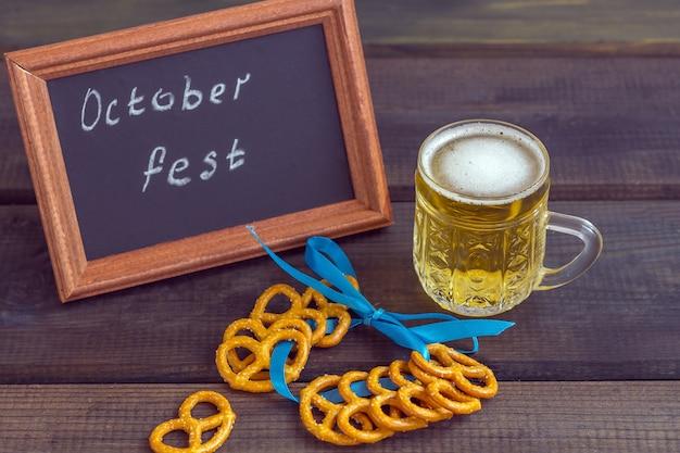 Festival de outubro. caneca de cerveja com salgadinhos de salgadinhos, bretzel e tabuleiro com as palavras