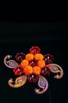 Festival indiano de diwali, flor de calêndula e lâmpadas coloridas de óleo em fundo preto