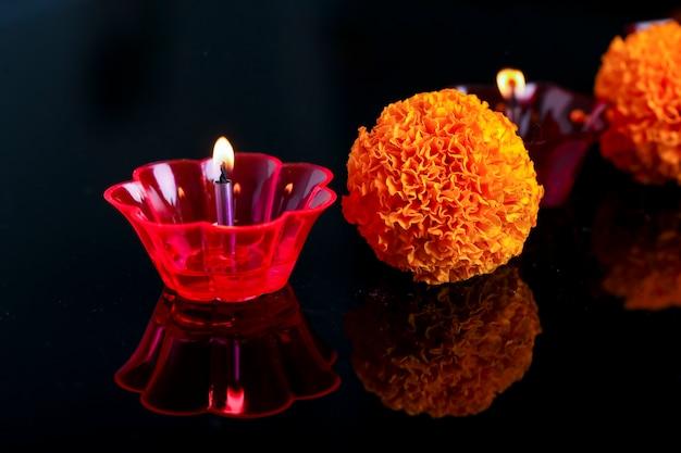 Festival indiano de diwali, flor de calêndula e lâmpadas coloridas de óleo sobre preto