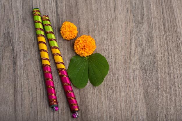 Festival indiano dussehra e navratri, mostrando folha dourada (bauhinia racemosa) e flores de calêndula com varas dandiya em uma mesa de madeira