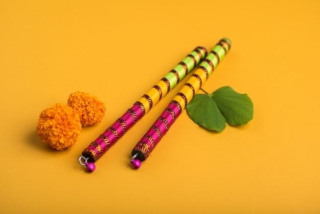 Festival indiano dussehra e navratri, mostrando folhas douradas (bauhinia racemosa) e flores de calêndula com varas dandiya.